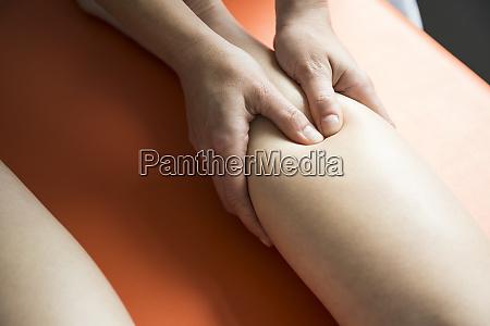 haende einer physiotherapeutin massieren den schaft