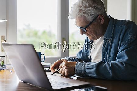 senior mann repariert laptop zu hause