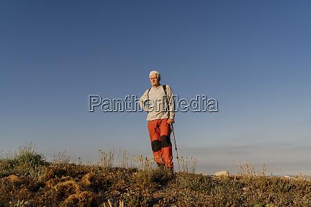 senior mann steht mit wanderstange auf