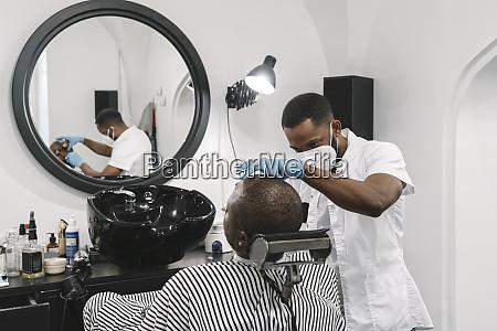 barbier traegt chirurgische maske und handschuhe
