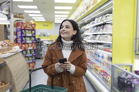 laechelnde junge frau mit smartphone lebensmitteleinkauf