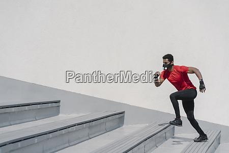 sportler traegt gesichtsmaske laeuft treppen