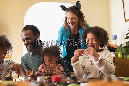 glueckliche familie schmueckt halloween cupcakes am