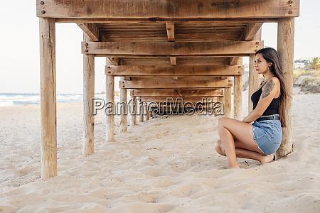 nachdenkliche teenager maedchen sitzen unter pier