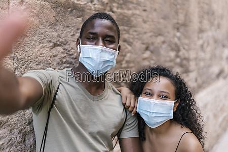 junges paar traegt masken waehrend selfie