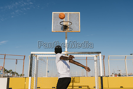 young, man, playing, basket, against, blue - 28744264