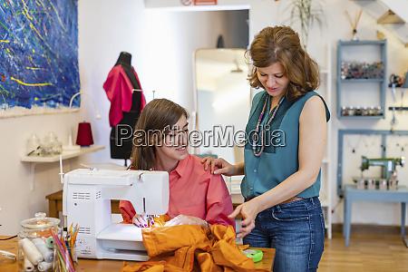 modedesignerin betreut die naehkuenste des auszubildenden