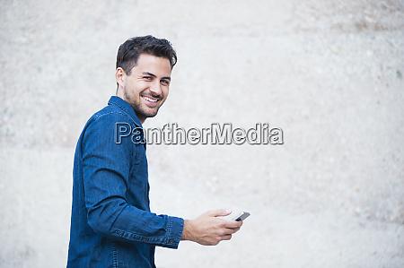 laechelnder junger mann mit smartphone