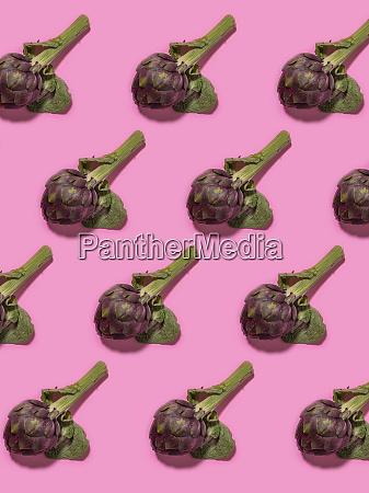 muster von artischockenkoepfen vor rosa hintergrund