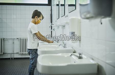 junge traegt maske auf schultoilette waschen