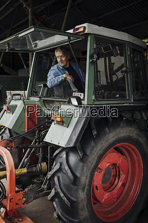 senior mann faehrt traktor auf einem