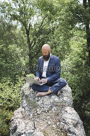 kahlkoepfiger baertiger geschaeftsmann der ueber laptop