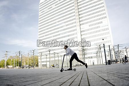 geschaeftsmann reitet kick scooter auf dem