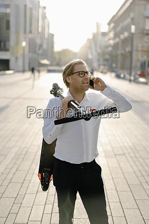 geschaeftsmann mit kick scooter am telefon