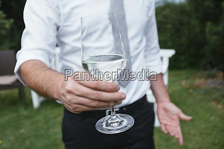mittlerer teil des mannes haelt glas