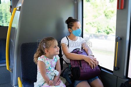 frau im bus traegt gesichtsmaske