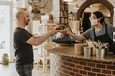kellnerin serviert essen in einer bar