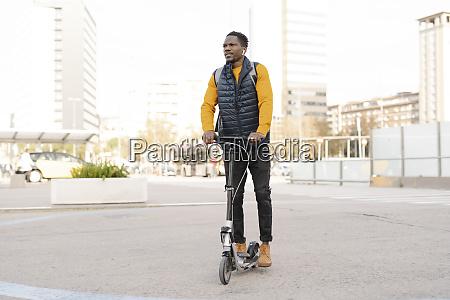 junger mann auf e scooter in
