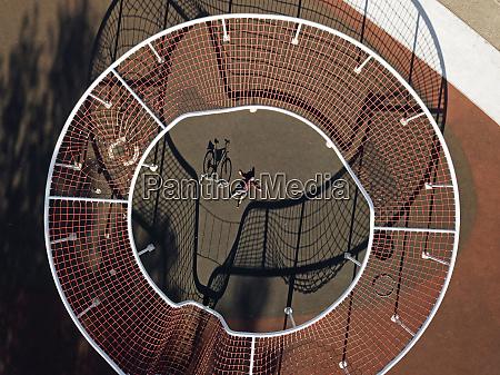 mann mit fahrrad im sportplatz luftbild