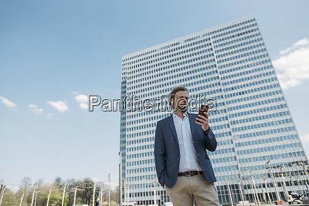 geschaeftsmann mit smartphone in der stadt