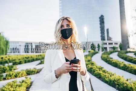 geschaeftsfrau traegt gesichtsmaske mit smartphone waehrend