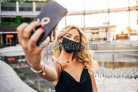 nahaufnahme der geschaeftsfrau traegt maske selfie