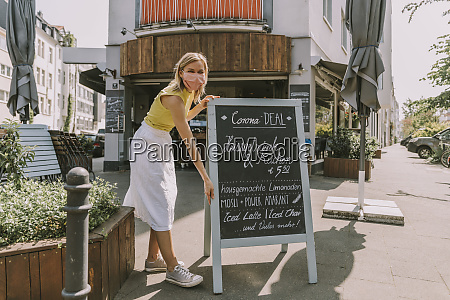 cafe besitzer traegt gesichtsmaske posting ein