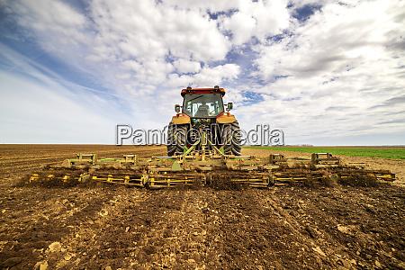 rueckansicht des landwirts im traktorpfpfluegen im