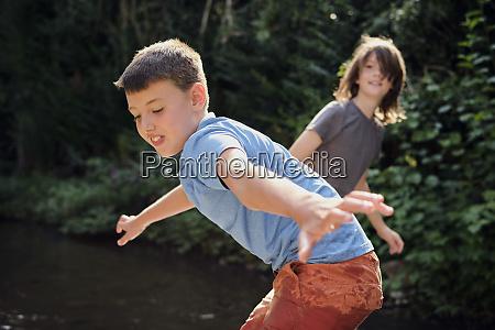 jungen spielen im bach im wald