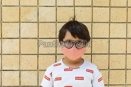 junge traegt rote maske vor der