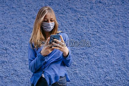 junge frau traegt maske mit smartphone