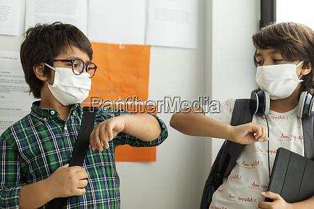 jungen tragen masken die ellenbogenstoss geben