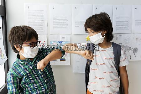 schueler tragen masken die ellenbogenstoss geben