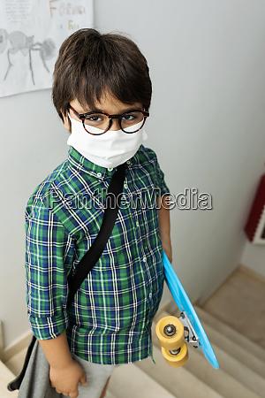 junge traegt maske halten skateboard waehrend