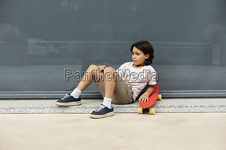 nachdenklicher junge mit skateboard entspannen auf