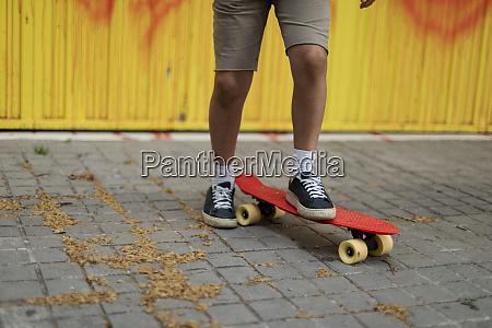 beine von jungen skateboarding auf fussweg