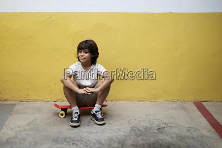 nachdenklicher junge sitzt auf skateboard gegen