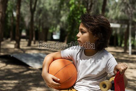 nachdenklicher junge mit basketball und skateboard