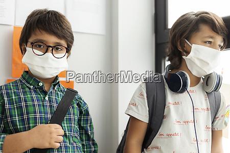 junge traegt maske stehend mit freund