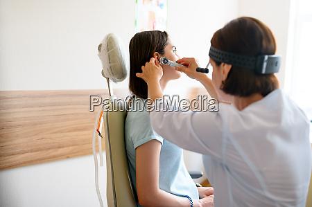 AErztin und patientin im buero ohrenuntersuchung