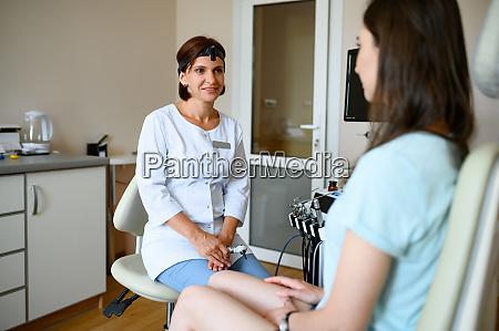 laechelnde laryngologein und patientin im stuhl