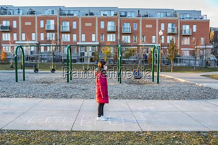 junges maedchen steht auf einem spielplatz