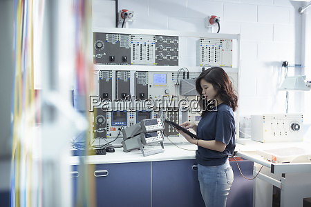 elektroingenieurin steht vor dem pruefstand der