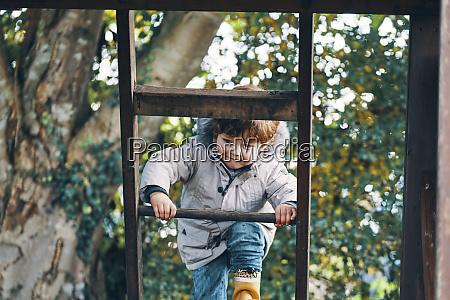 ein kind klettert auf eine leiter