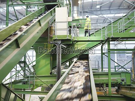 arbeiter kontrollieren foerderbaender mit altpapier in