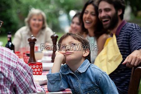 gelangweilter junge beim outdoor familienessen