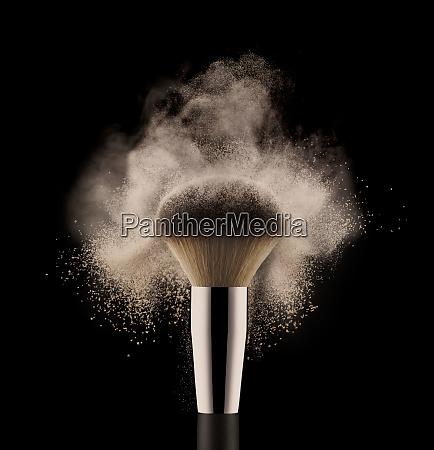 nahaufnahme der kosmetischen pulverbuerste auf schwarzem