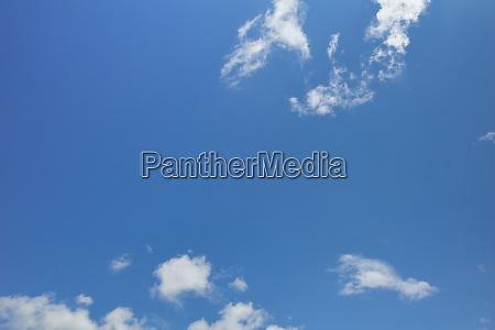 zerrissene weisse wolken am friedlichen blauen