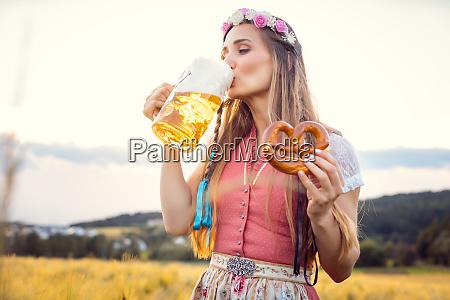 frau in traditioneller kleidung trinkt bier