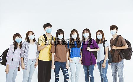 junge studentengruppe traegt schuetzende medizinische gesichtsmasken